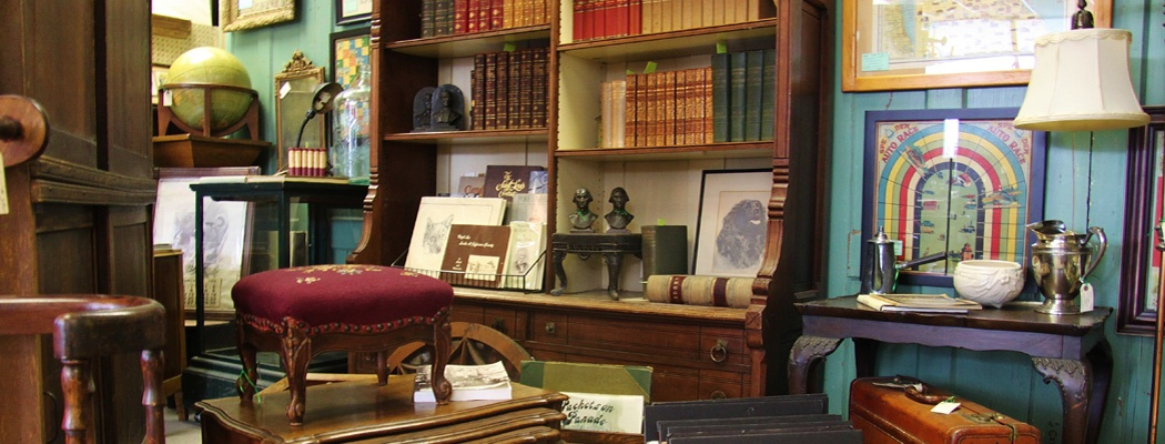 Antiques, collectibles, or vintage items including vintage books, antique furniture, luggage, and framed art on display by Dealer 26 at Warson Woods Antiques Gallery in St. Louis.